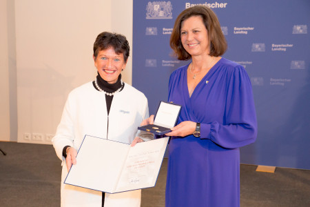 Inge Aures nimmt die Medaille von Landtagspräsidentin Ilse Aigner entgegen